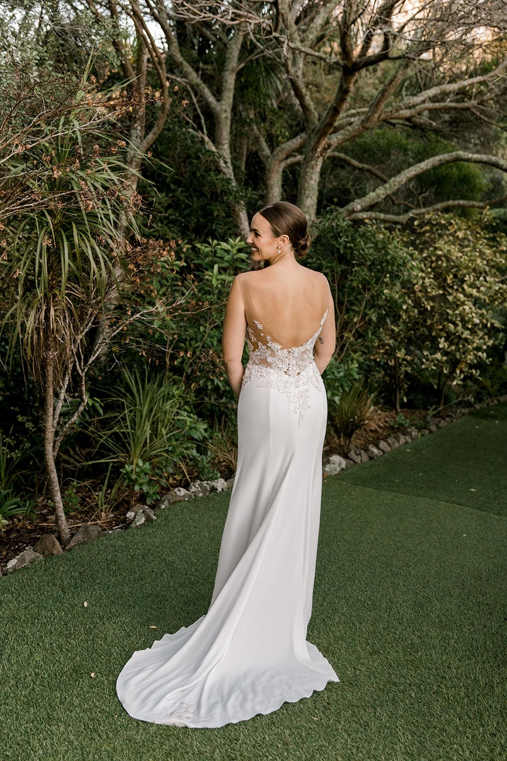 Samantha Wedding Dress from Vinka Design. This beautiful wedding dress has a nude sheer illusion strapless neckline made from fine Italian tulle. Low sheer back & structured bodice, & soft crepe train. Back detail of gown. Photographed in Landscaped garden.