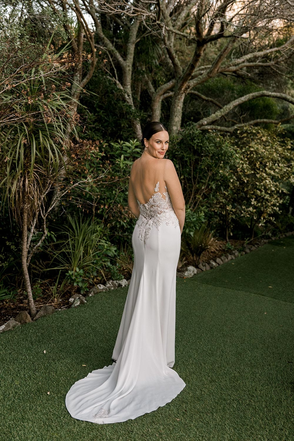 Samantha Wedding Dress from Vinka Design. This beautiful wedding dress has a nude sheer illusion strapless neckline made from fine Italian tulle. Low sheer back & structured bodice, & soft crepe train. Full length dress from the back with train extended. Photographed in Landscaped garden.