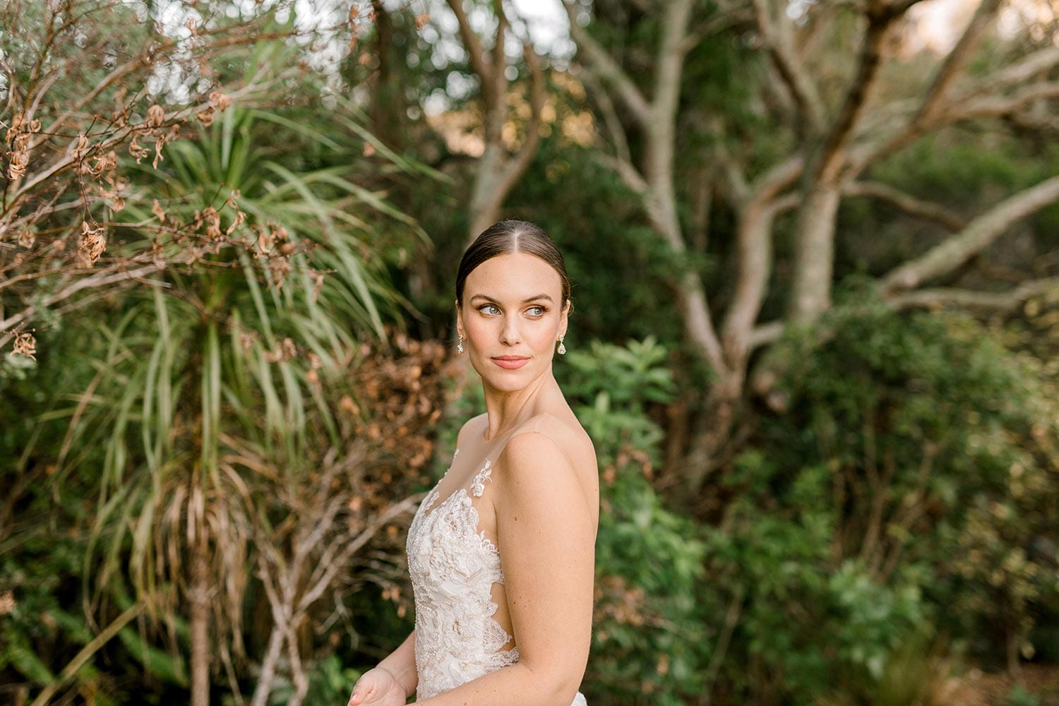 Samantha Wedding Dress from Vinka Design. This beautiful wedding dress has a nude sheer illusion strapless neckline made from fine Italian tulle. Low sheer back & structured bodice, & soft crepe train. Close up detail of bodice from the side. Photographed in Landscaped garden.