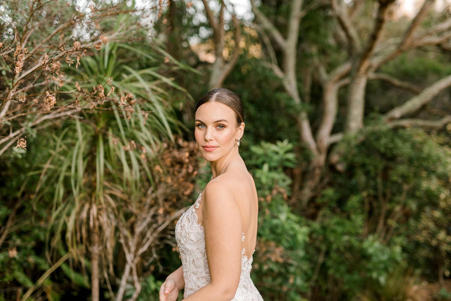 Samantha Wedding Dress from Vinka Design. This beautiful wedding dress has a nude sheer illusion strapless neckline made from fine Italian tulle. Low sheer back & structured bodice, & soft crepe train. Detail of bodice from the side. Photographed in Landscaped garden.