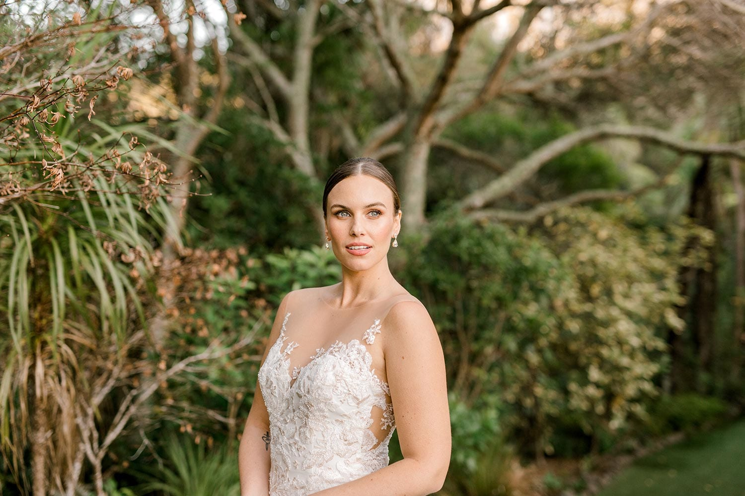 Samantha Wedding Dress from Vinka Design. This beautiful wedding dress has a nude sheer illusion strapless neckline made from fine Italian tulle. Low sheer back & structured bodice, & soft crepe train. Detail of bodice from the front. Photographed in Landscaped garden.
