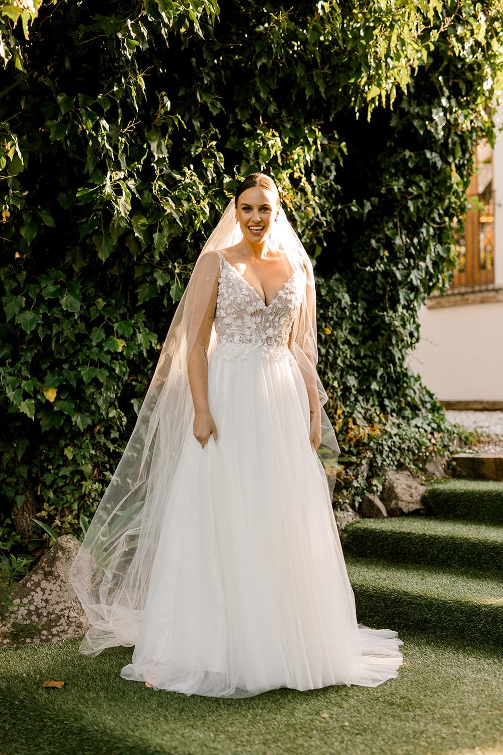Serena Wedding Gown from Vinka Design - Classic & feminine wedding gown. Deep V-neckline semi-sheer structured bodice appliqued with flowers & leaves. Dreamy layered soft tulle skirt with side-split. Photograph in landscaped gardens.