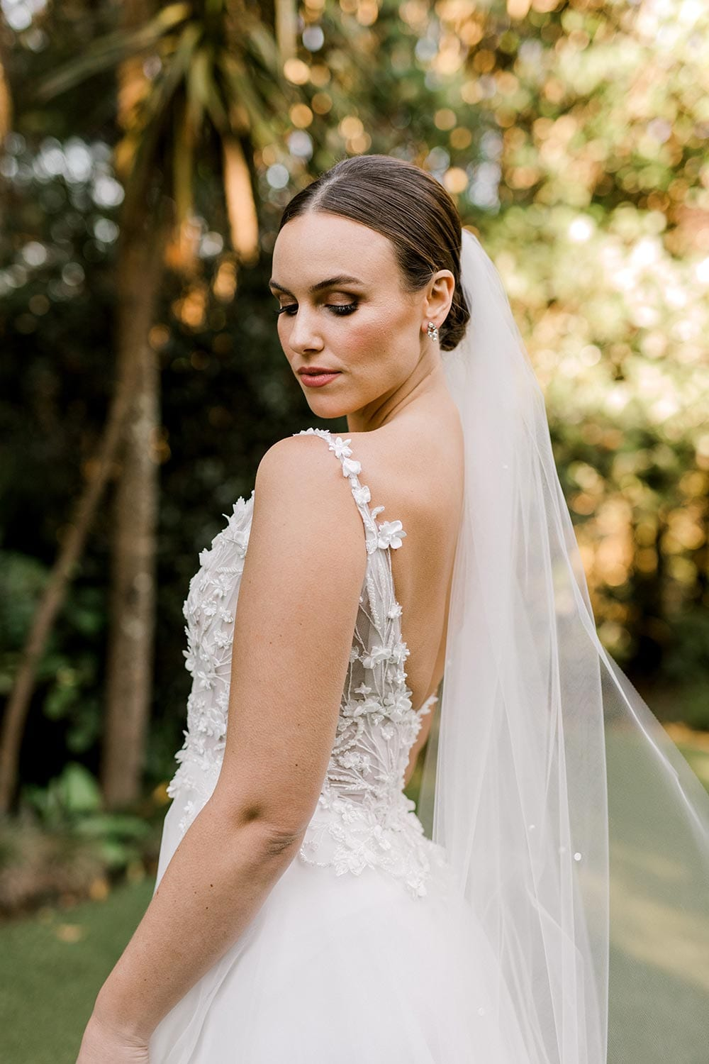 Serena Wedding Gown from Vinka Design - Classic & feminine wedding gown. Deep V-neckline semi-sheer structured bodice appliqued with flowers & leaves. Dreamy layered soft tulle skirt with side-split. Side detail of dress. Photograph in landscaped gardens.