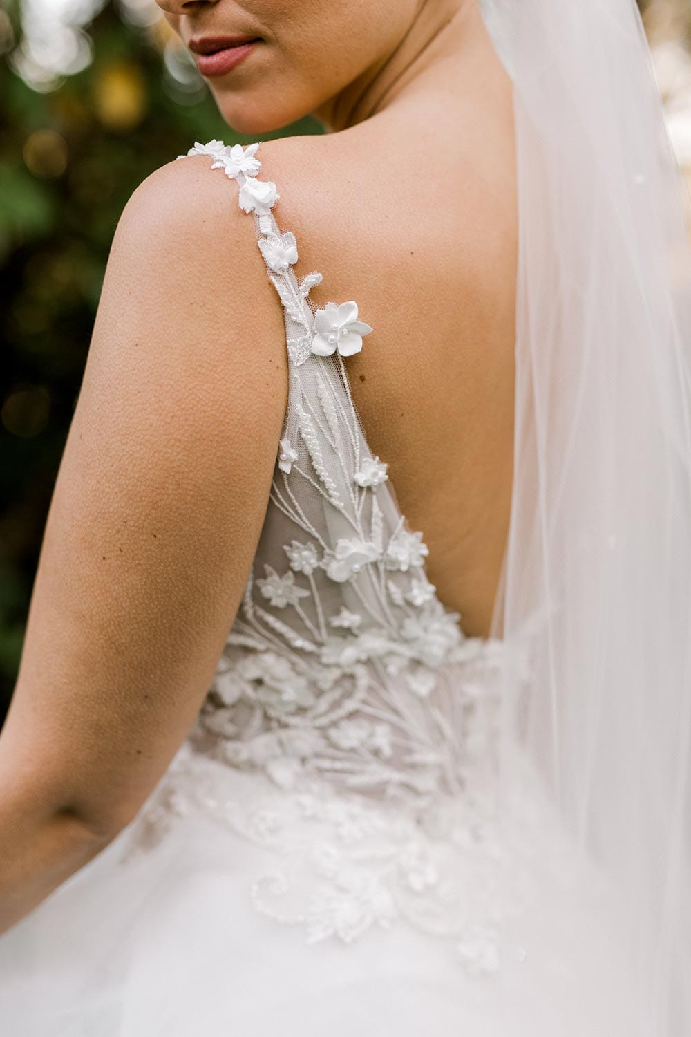 Serena Wedding Gown from Vinka Design - Classic & feminine wedding gown. Deep V-neckline semi-sheer structured bodice appliqued with flowers & leaves. Dreamy layered soft tulle skirt with side-split. Close up detail of bodice and straps. Photograph in landscaped gardens.