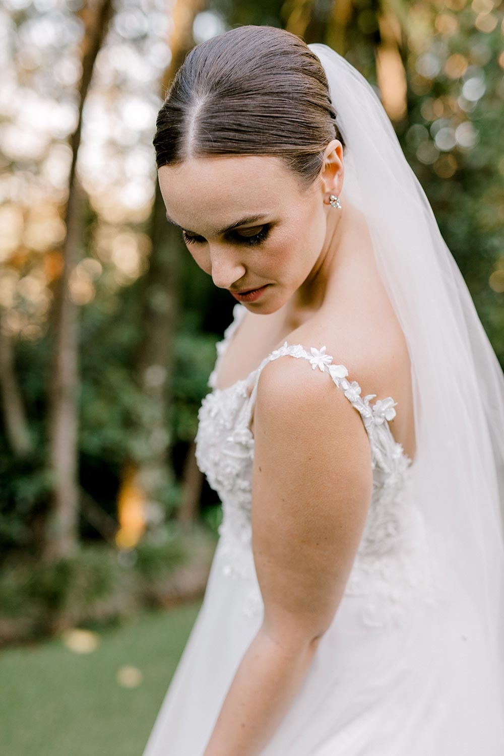 Serena Wedding Gown from Vinka Design - Classic & feminine wedding gown. Deep V-neckline semi-sheer structured bodice appliqued with flowers & leaves. Dreamy layered soft tulle skirt with side-split. Close up detail of bodice and shoulder straps. Photograph in landscaped gardens.
