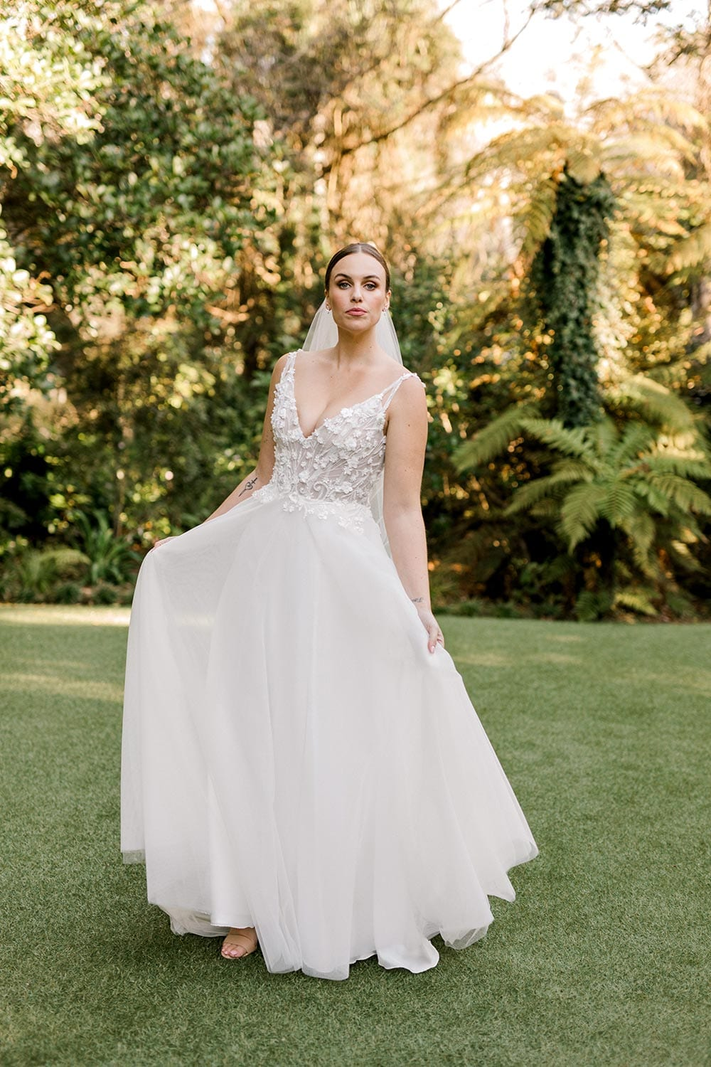 Serena Wedding Gown from Vinka Design - Classic & feminine wedding gown. Deep V-neckline semi-sheer structured bodice appliqued with flowers & leaves. Dreamy layered soft tulle skirt with side-split. Full view with skirt being held out. Photograph in landscaped gardens.