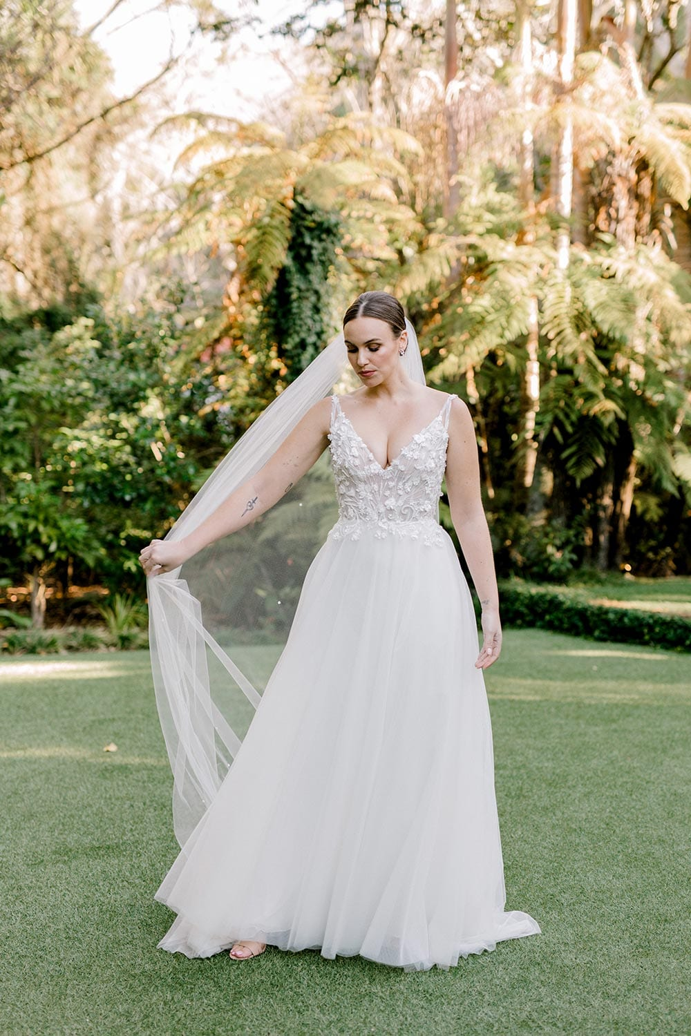Serena Wedding Gown from Vinka Design - Classic & feminine wedding gown. Deep V-neckline semi-sheer structured bodice appliqued with flowers & leaves. Dreamy layered soft tulle skirt with side-split. Full view of tulle skirt. Photograph in landscaped gardens.