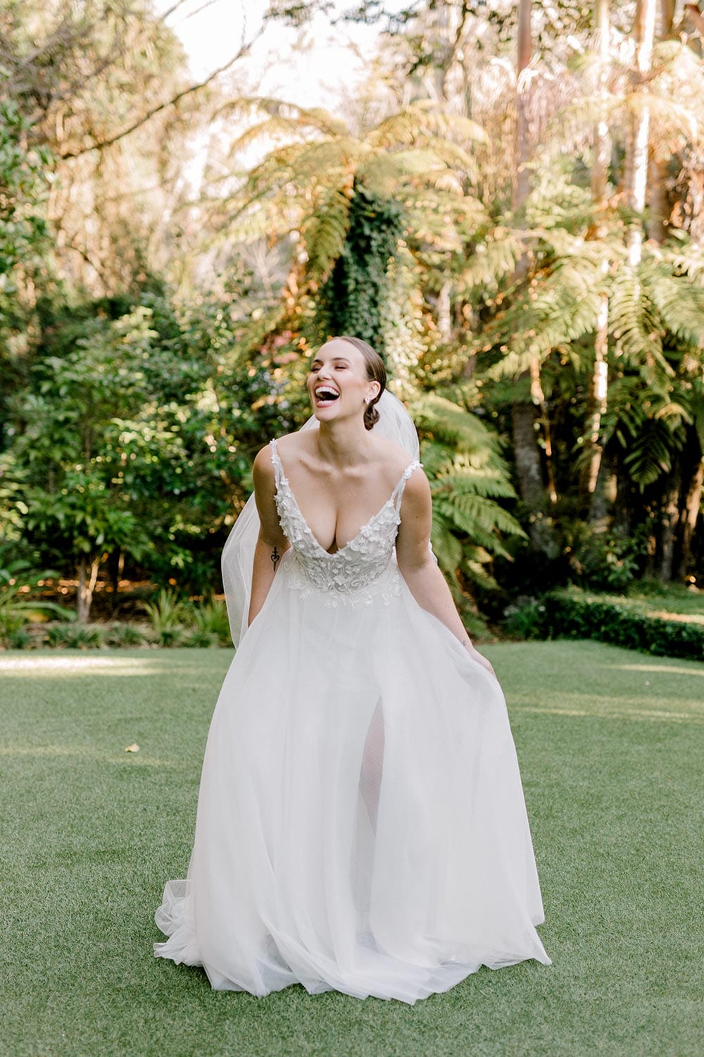 Serena Wedding Gown from Vinka Design - Classic & feminine wedding gown. Deep V-neckline semi-sheer structured bodice appliqued with flowers & leaves. Dreamy layered soft tulle skirt with side-split. Model leaning forward. Photograph in landscaped gardens.