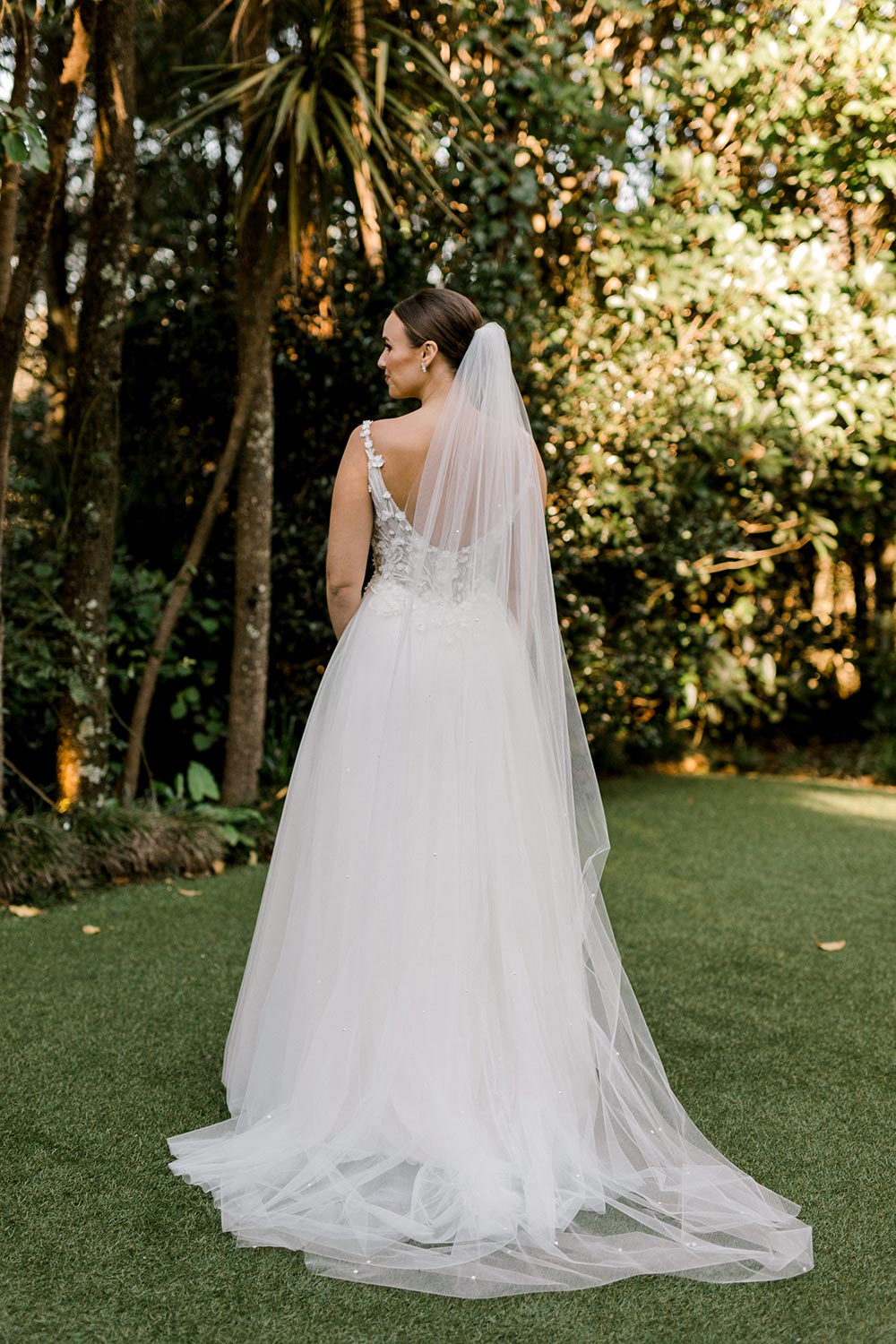 Serena Wedding Gown from Vinka Design - Classic & feminine wedding gown. Deep V-neckline semi-sheer structured bodice appliqued with flowers & leaves. Dreamy layered soft tulle skirt with side-split. Full length detail of back of dress. Photograph in landscaped gardens.