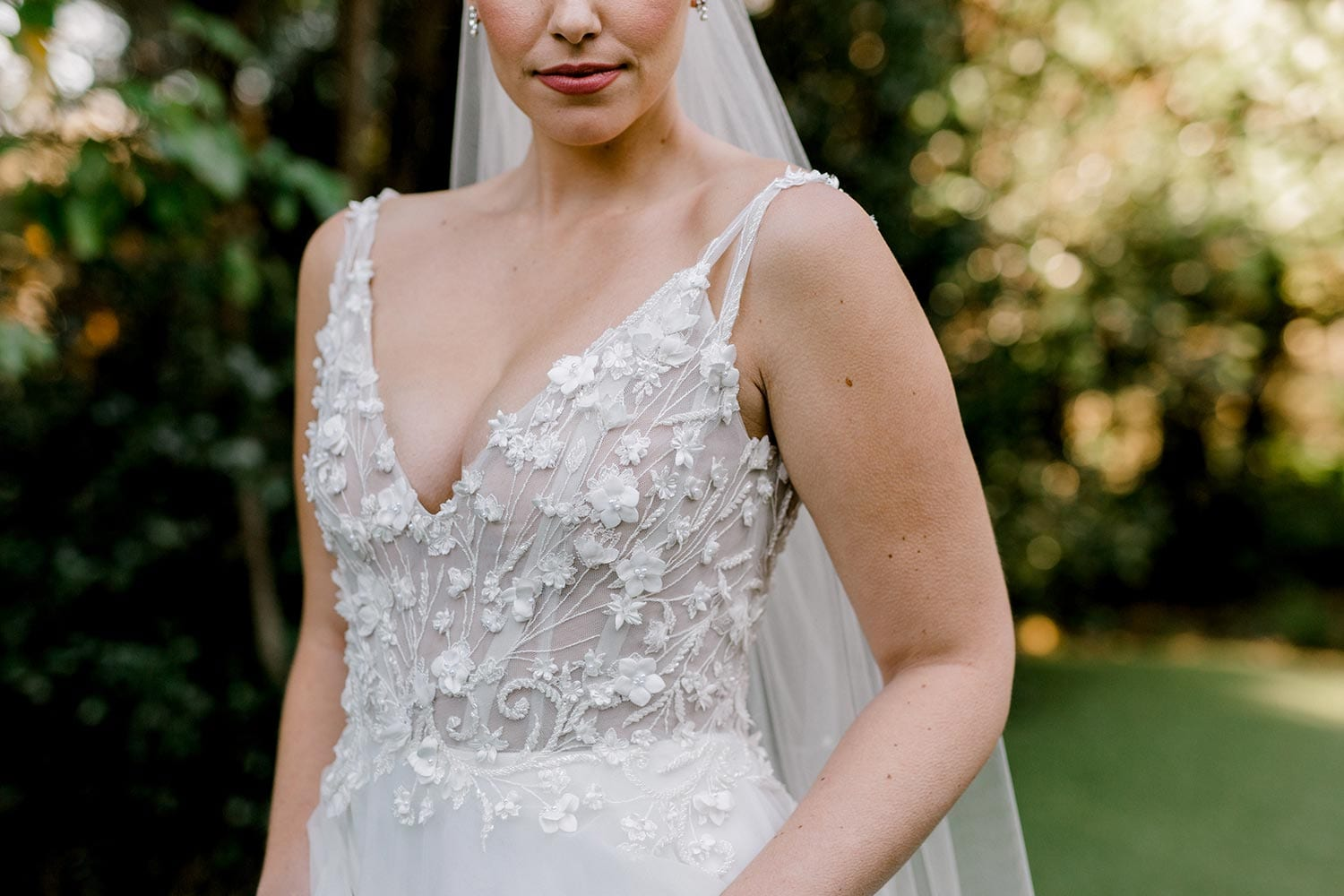 Serena Wedding Gown from Vinka Design - Classic & feminine wedding gown. Deep V-neckline semi-sheer structured bodice appliqued with flowers & leaves. Dreamy layered soft tulle skirt with side-split. Close up detail of bodice V-neckline. Photograph in landscaped gardens.