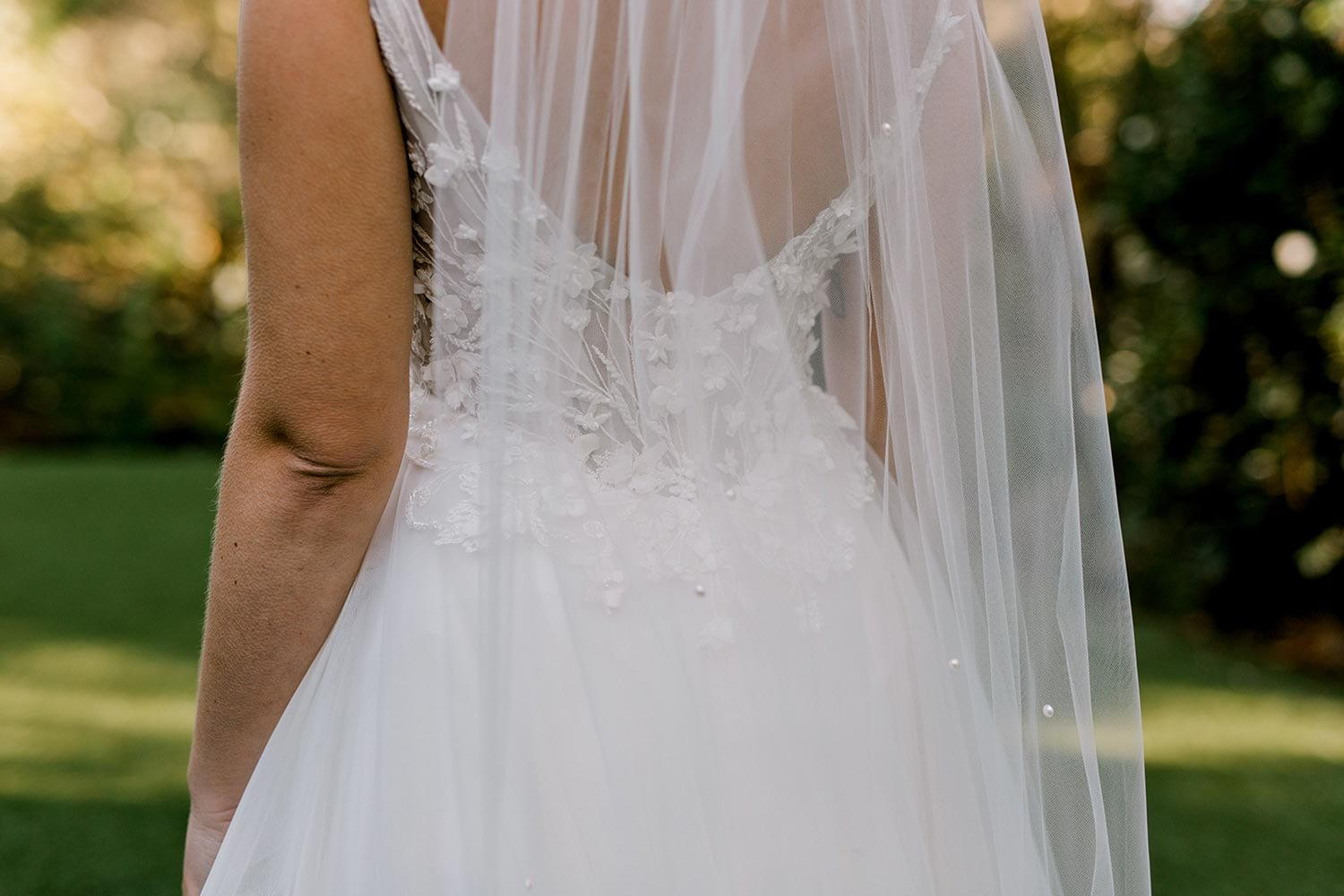 Serena Wedding Gown from Vinka Design - Classic & feminine wedding gown. Deep V-neckline semi-sheer structured bodice appliqued with flowers & leaves. Dreamy layered soft tulle skirt with side-split. Close up detail of bodice and skirt at back. Photograph in landscaped gardens.