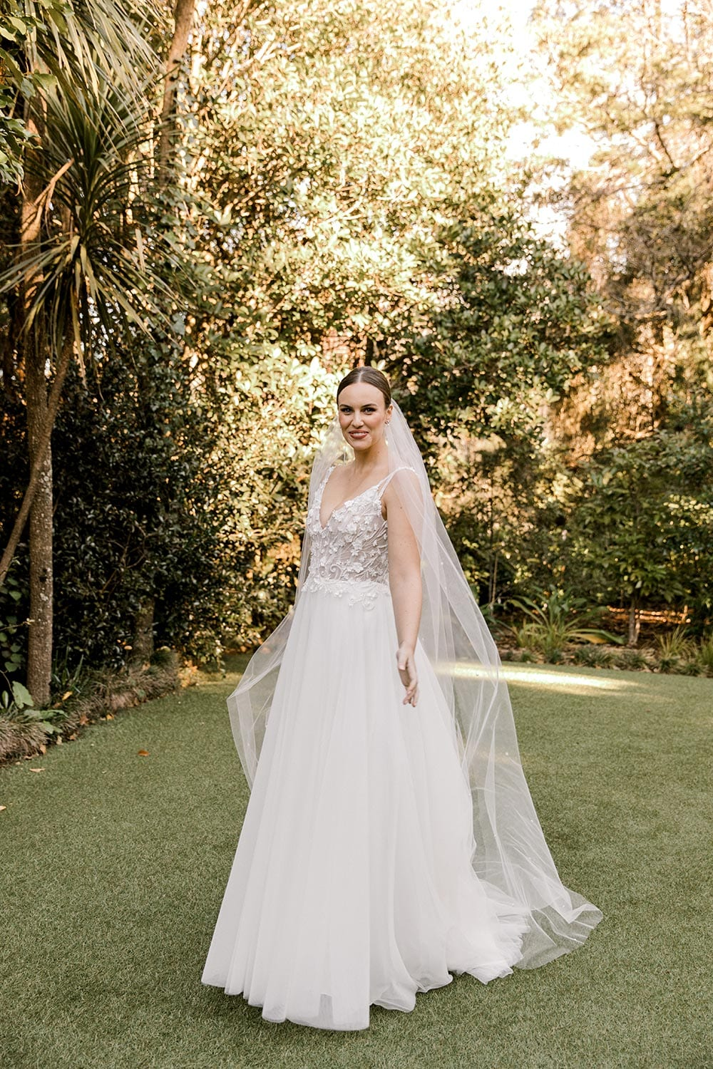 Serena Wedding Gown from Vinka Design - Classic & feminine wedding gown. Deep V-neckline semi-sheer structured bodice appliqued with flowers & leaves. Dreamy layered soft tulle skirt with side-split. Full length photo of model in dress. Photograph in landscaped gardens.