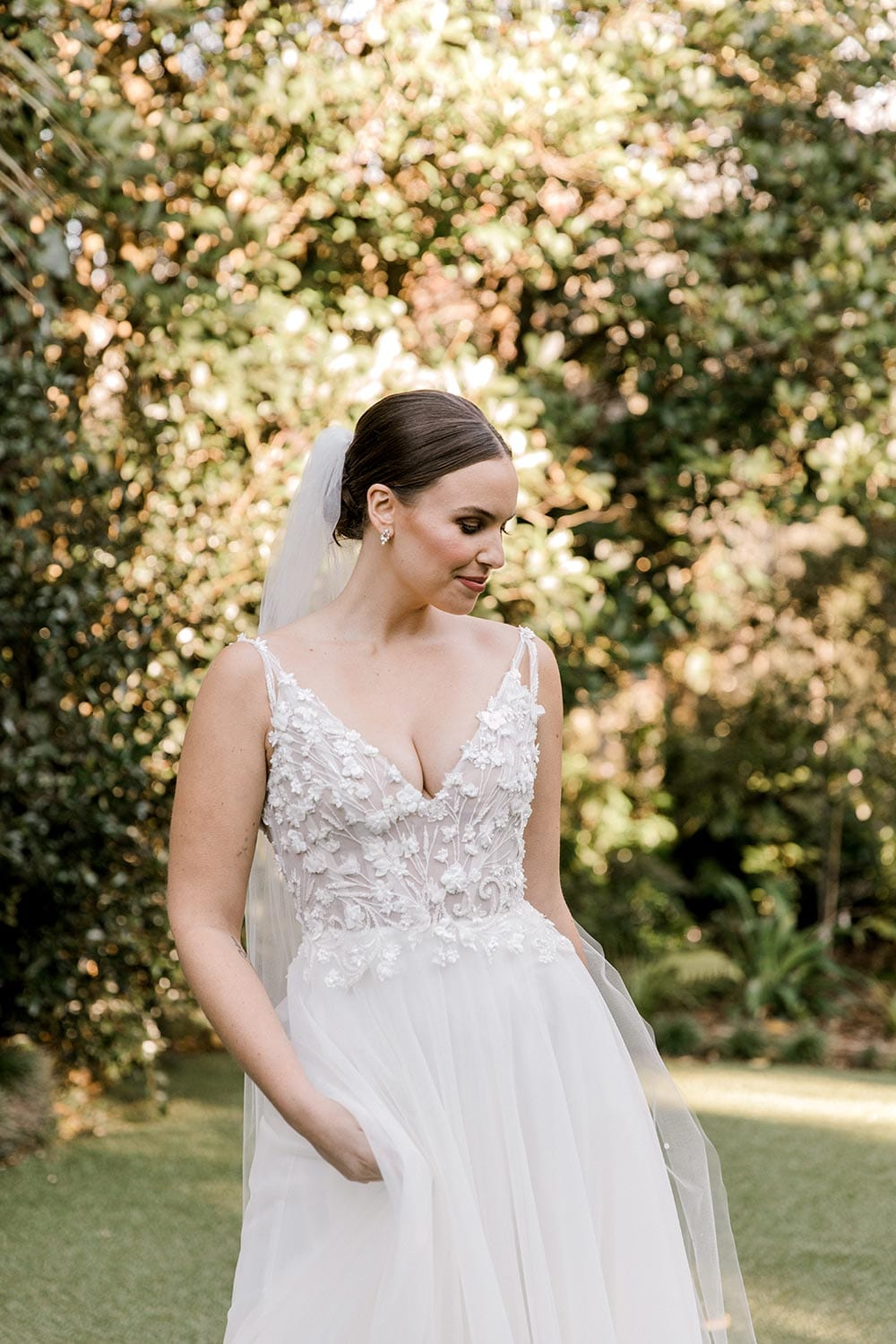 Serena Wedding Gown from Vinka Design - Classic & feminine wedding gown. Deep V-neckline semi-sheer structured bodice appliqued with flowers & leaves. Dreamy layered soft tulle skirt with side-split. Close up of top half showing bodice detail. Photograph in landscaped gardens.