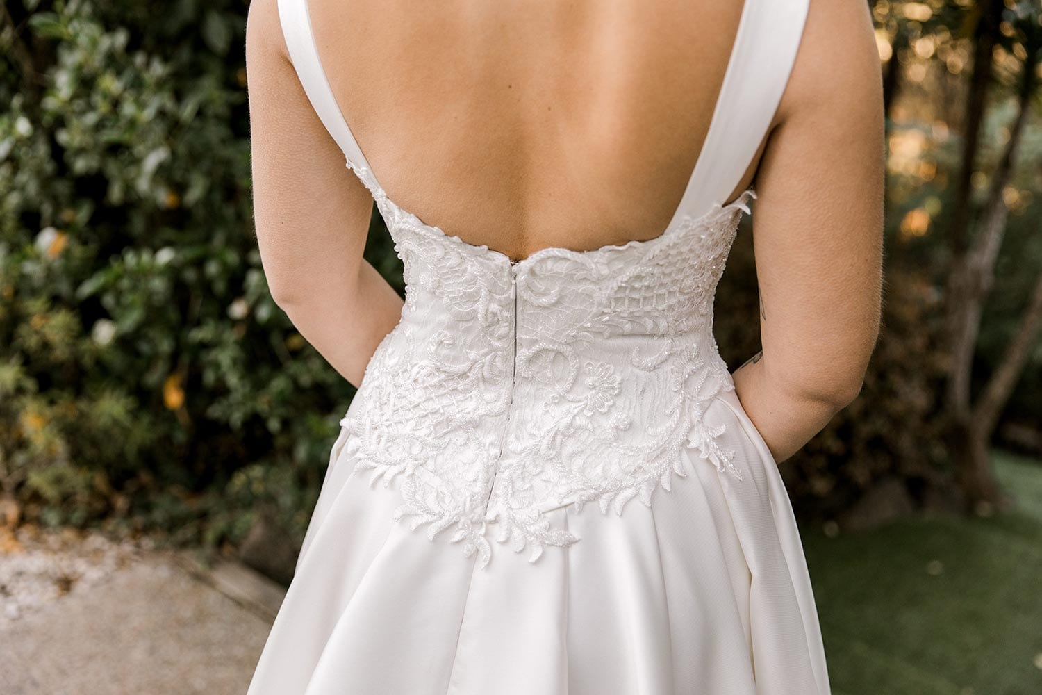 Victoria Wedding Dress by Vinka Design - Dramatic & luxurious Mikado silk wedding dress. Sweetheart neckline, sculptured & fitted bodice, & full skirt with irregular folds emphasize the waist. Photographed in landscaped gardens - lower back detail.