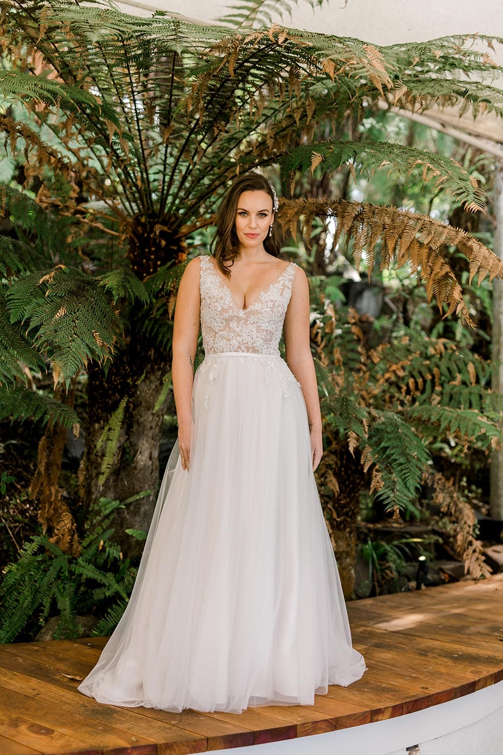 Vivian Wedding gown from Vinka Design - A stunning gown with a deep V-neckline on both the front & back. Fitted semi-sheer nude bodice embellished with a beaded floral lace, a soft layered tulle skirt. Worn in conservatory with fern background, portrait.