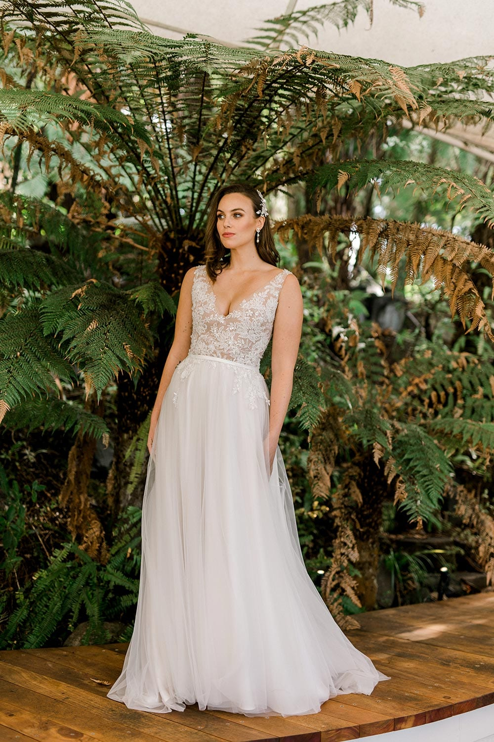Vivian Wedding gown from Vinka Design - A stunning gown with a deep V-neckline on both the front & back. Fitted semi-sheer nude bodice embellished with a beaded floral lace, a soft layered tulle skirt. Worn in conservatory with fern background, dress flowing to the ground.