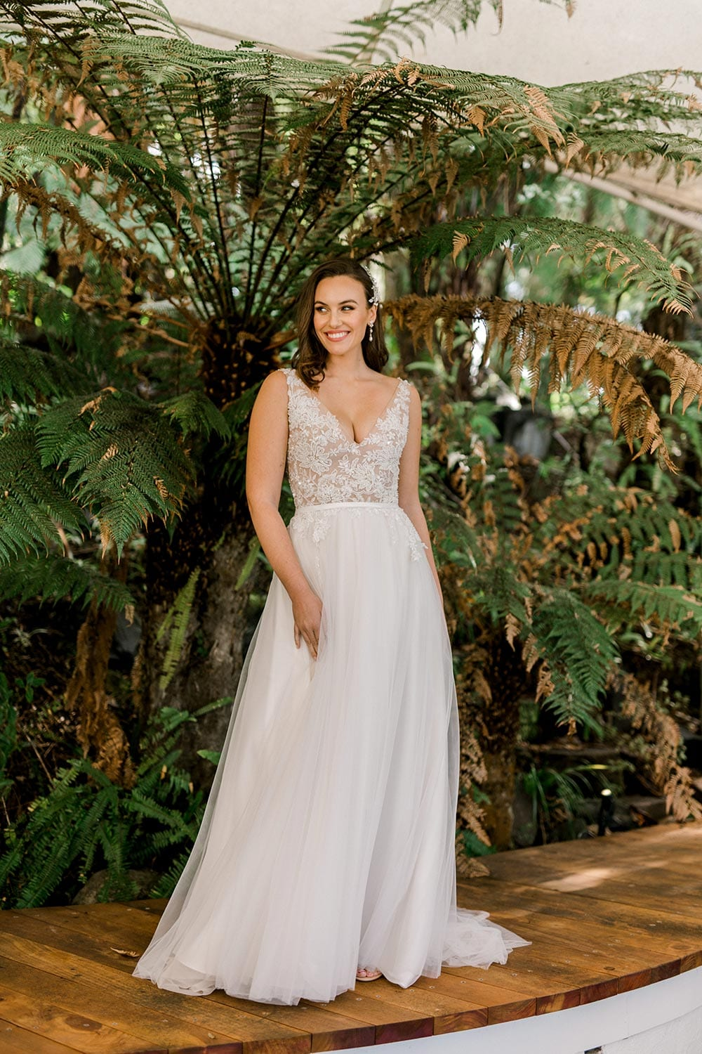 Vivian Wedding gown from Vinka Design - A stunning gown with a deep V-neckline on both the front & back. Fitted semi-sheer nude bodice embellished with a beaded floral lace, a soft layered tulle skirt. Worn in conservatory with fern background, hands to the side.