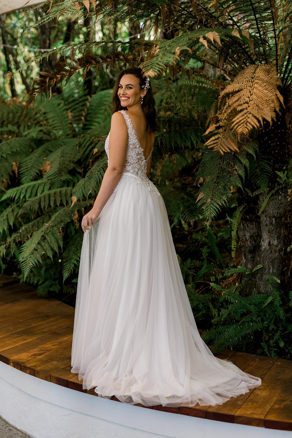 Vivian Wedding gown from Vinka Design - A stunning gown with a deep V-neckline on both the front & back. Fitted semi-sheer nude bodice embellished with a beaded floral lace, a soft layered tulle skirt. Worn in conservatory with fern background, model facing away showing train.