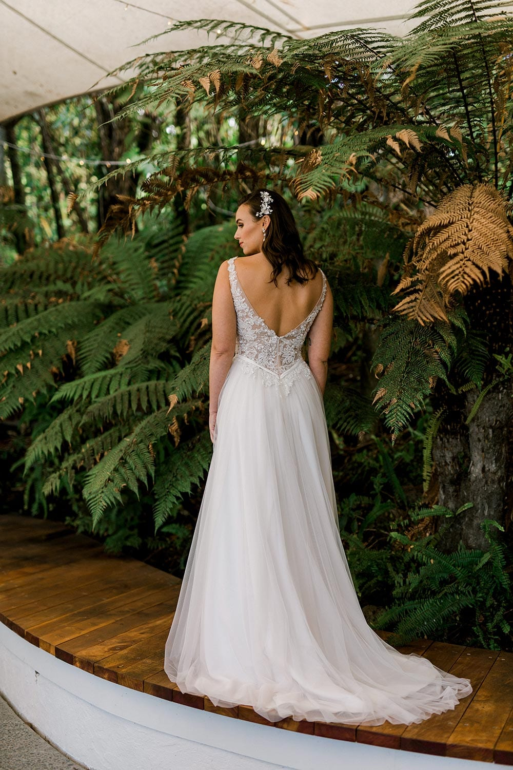 Vivian Wedding gown from Vinka Design - A stunning gown with a deep V-neckline on both the front & back. Fitted semi-sheer nude bodice embellished with a beaded floral lace, a soft layered tulle skirt. Worn in conservatory with fern background, model facing away.
