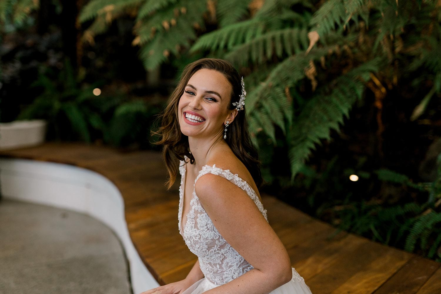 Vivian Wedding gown from Vinka Design - A stunning gown with a deep V-neckline on both the front & back. Fitted semi-sheer nude bodice embellished with a beaded floral lace, a soft layered tulle skirt. Worn in conservatory with fern background, close up of V-neckline.