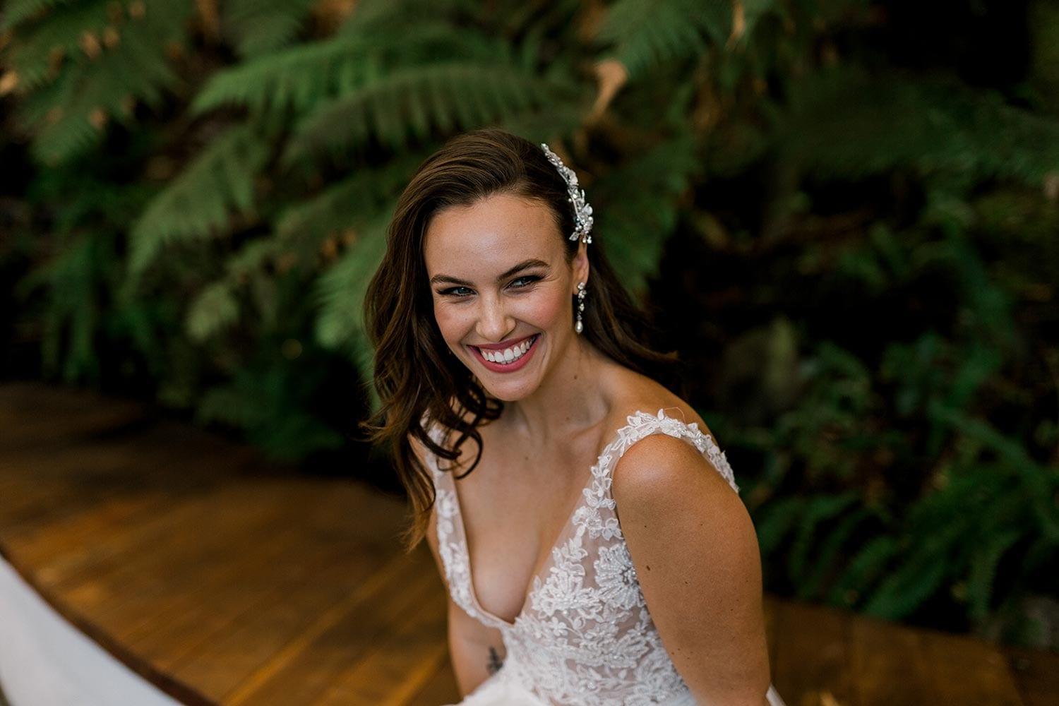 Vivian Wedding gown from Vinka Design - A stunning gown with a deep V-neckline on both the front & back. Fitted semi-sheer nude bodice embellished with a beaded floral lace, a soft layered tulle skirt. Worn in conservatory with fern background, shoulders and V-neckline.