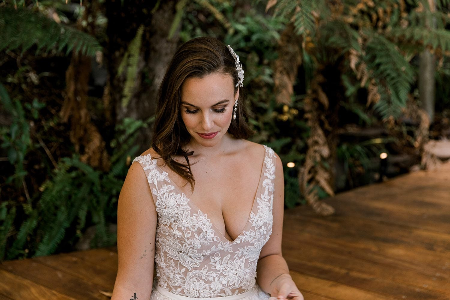 Vivian Wedding gown from Vinka Design - A stunning gown with a deep V-neckline on both the front & back. Fitted semi-sheer nude bodice embellished with a beaded floral lace, a soft layered tulle skirt. Worn in conservatory with fern background, head to waist showing V-neckline detail.