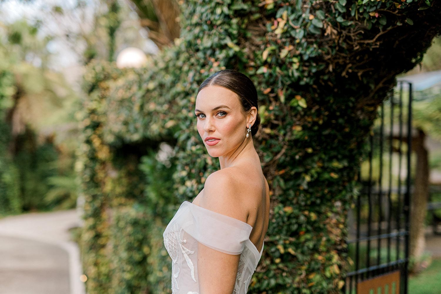 Zoe wedding dress by Vinka Design - a romantic & dreamy off-shoulder gown with a structured, boned bodice, a full lace & tulle skirt. Semi-sheer bodice with tulle off-shoulder detailing and satin belt. Worn in gardens.
