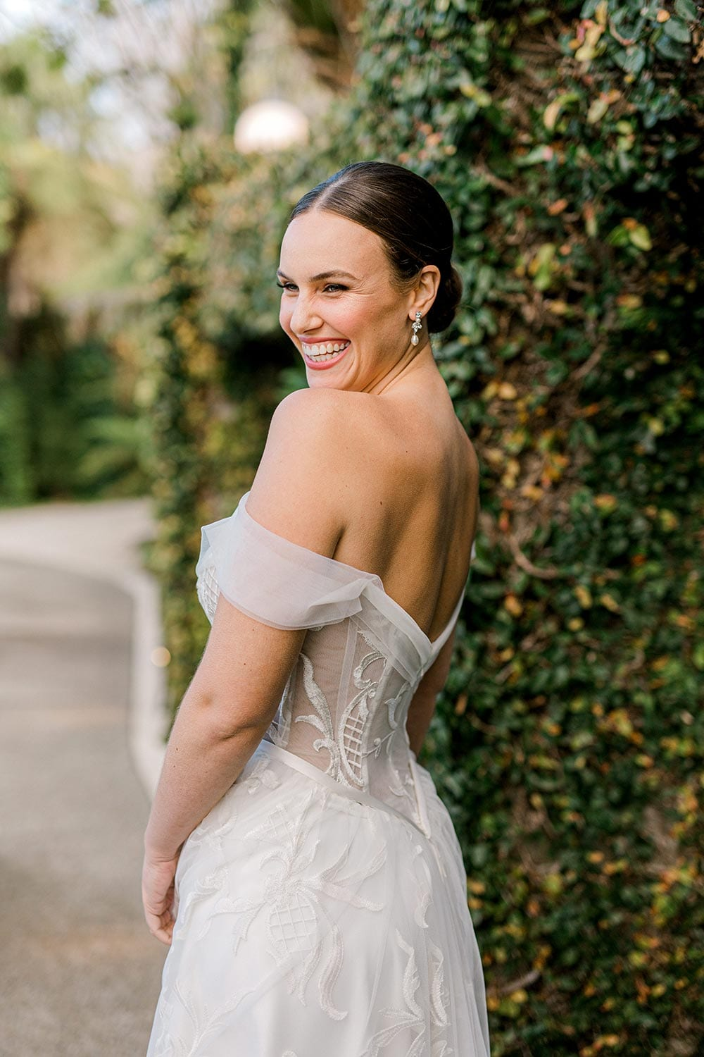 Zoe wedding dress by Vinka Design - a romantic & dreamy off-shoulder gown with a structured, boned bodice, a full lace & tulle skirt. Semi-sheer bodice with tulle off-shoulder detailing and satin belt. Worn outdoors.