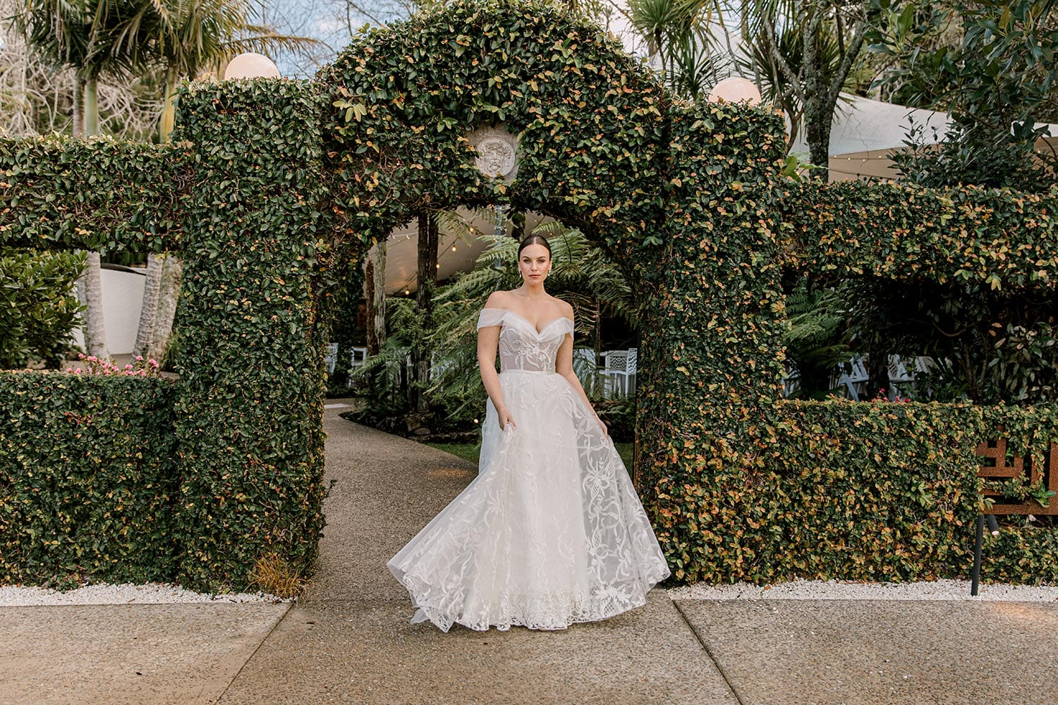 Zoe wedding dress by Vinka Design - a romantic & dreamy off-shoulder gown with a structured, boned bodice, a full lace & tulle skirt. Semi-sheer bodice with tulle off-shoulder detailing and satin belt. Worn in garden archway.