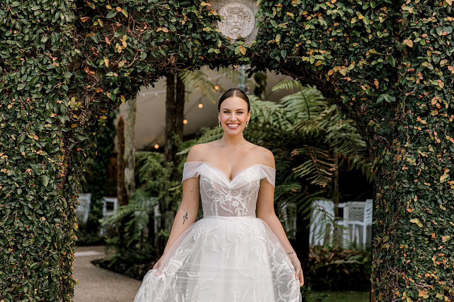 Zoe wedding dress by Vinka Design - a romantic & dreamy off-shoulder gown with a structured, boned bodice, a full lace & tulle skirt. Semi-sheer bodice with tulle off-shoulder detailing and satin belt. Worn in garden archway, landscape.