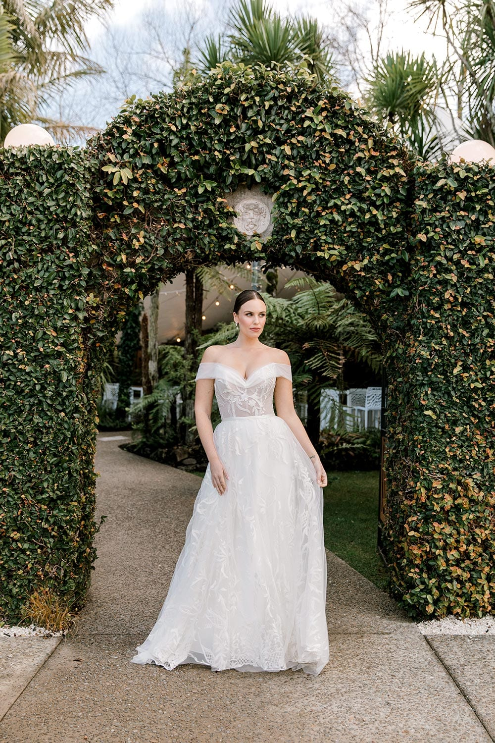 Zoe wedding dress by Vinka Design - a romantic & dreamy off-shoulder gown with a structured, boned bodice, a full lace & tulle skirt. Semi-sheer bodice with tulle off-shoulder detailing and satin belt. Worn in garden archway, portrait.