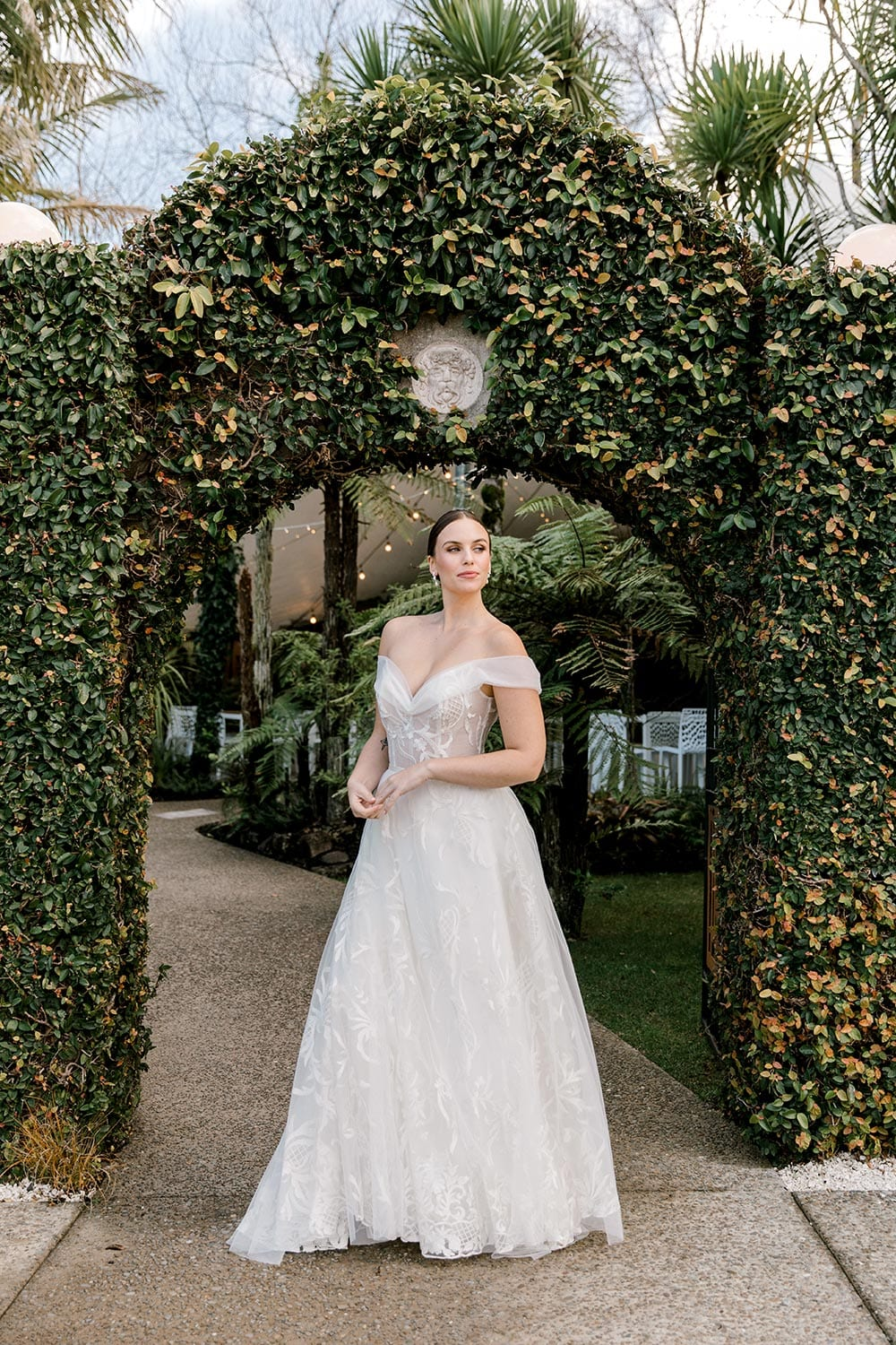 Zoe wedding dress by Vinka Design - a romantic & dreamy off-shoulder gown with a structured, boned bodice, a full lace & tulle skirt. Semi-sheer bodice with tulle off-shoulder detailing and satin belt. Worn in green garden archway.