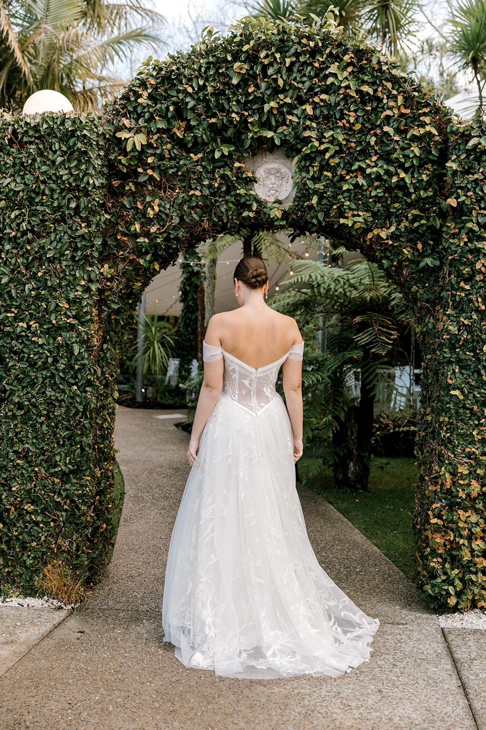 Zoe wedding dress by Vinka Design - a romantic & dreamy off-shoulder gown with a structured, boned bodice, a full lace & tulle skirt. Semi-sheer bodice with tulle off-shoulder detailing and satin belt. Worn in green garden archway, model facing away to show back.