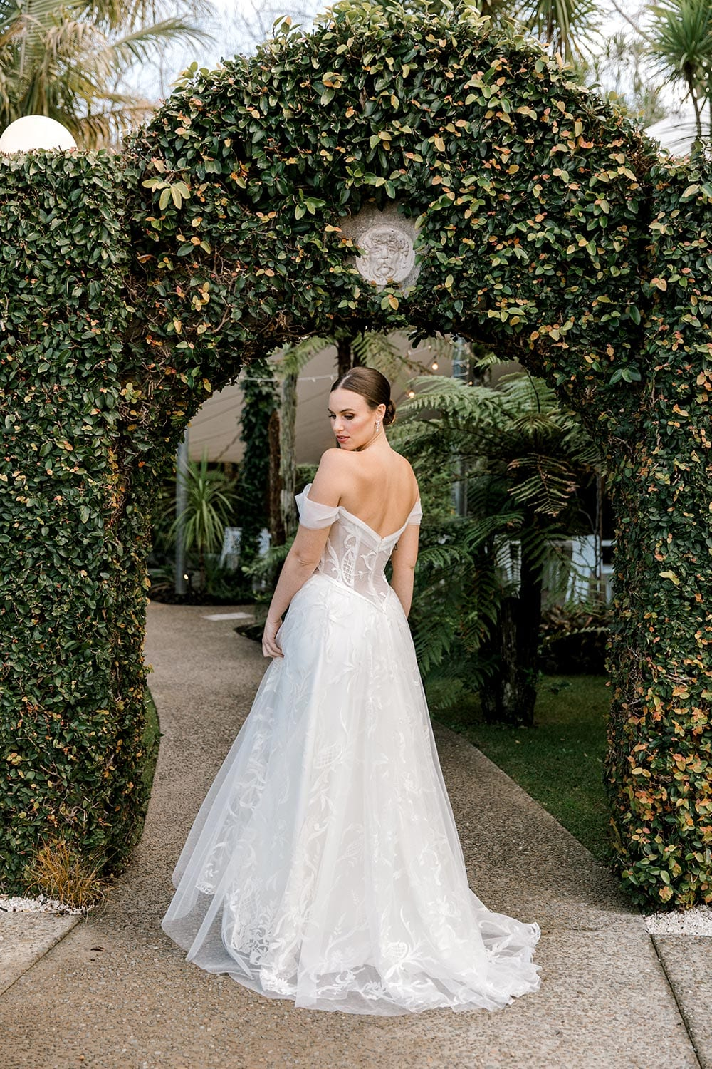 Zoe wedding dress by Vinka Design - a romantic & dreamy off-shoulder gown with a structured, boned bodice, a full lace & tulle skirt. Semi-sheer bodice with tulle off-shoulder detailing and satin belt. Worn in green garden archway, model looking back over shoulder.