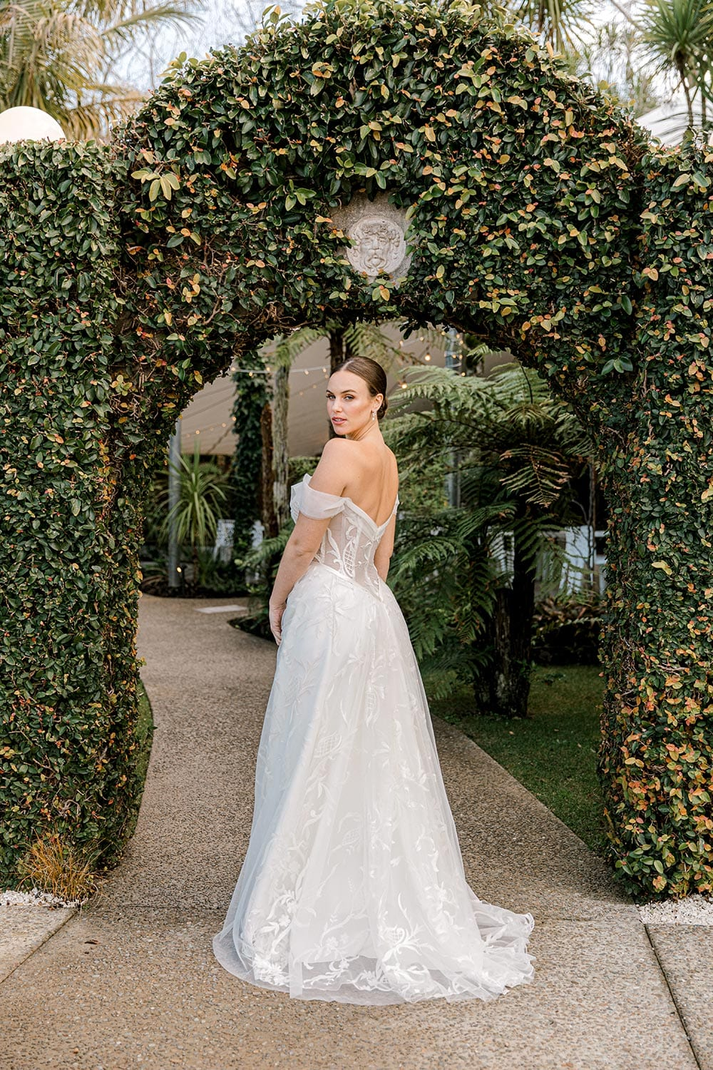 Zoe wedding dress by Vinka Design - a romantic & dreamy off-shoulder gown with a structured, boned bodice, a full lace & tulle skirt. Semi-sheer bodice with tulle off-shoulder detailing and satin belt. Worn in green garden archway, model looking back over shoulder showing train.