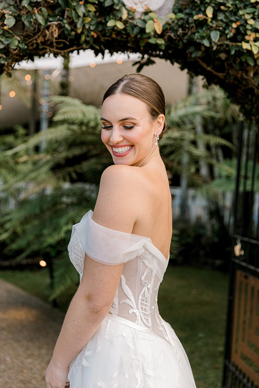 Zoe wedding dress by Vinka Design - a romantic & dreamy off-shoulder gown with a structured, boned bodice, a full lace & tulle skirt. Semi-sheer bodice with tulle off-shoulder detailing and satin belt. Worn in green garden archway, model looking back over shoulder close up.