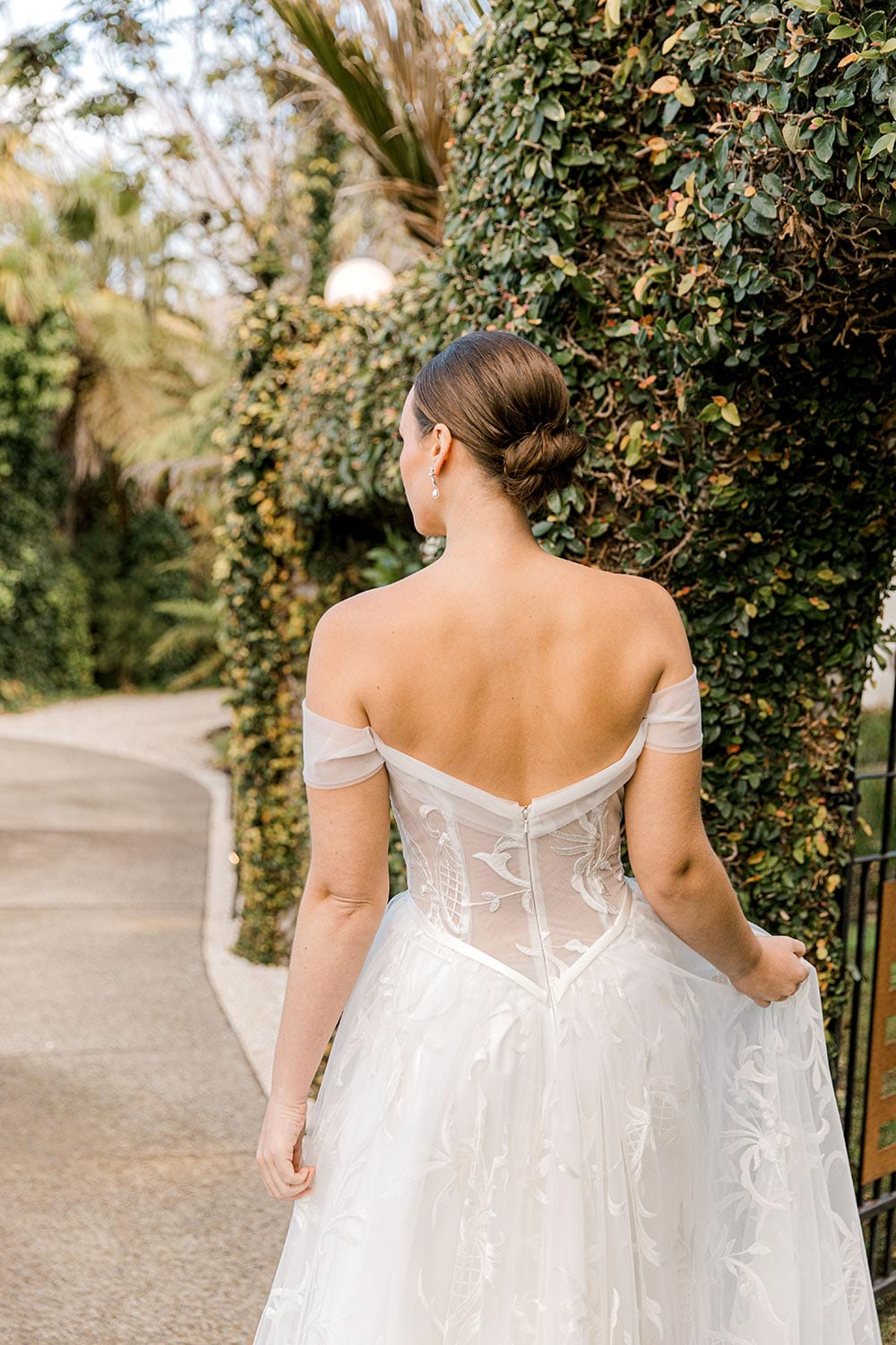 Zoe wedding dress by Vinka Design - a romantic & dreamy off-shoulder gown with a structured, boned bodice, a full lace & tulle skirt. Semi-sheer bodice with tulle off-shoulder detailing and satin belt. Worn in green garden archway, model facing away -close up.