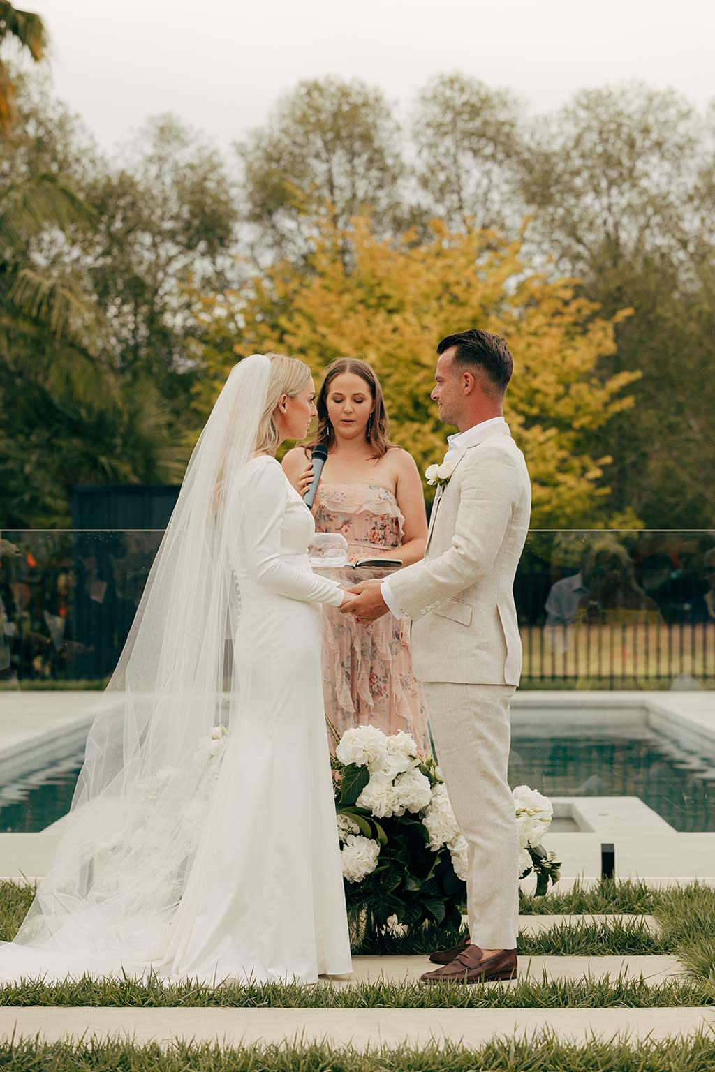 Vinka Design Bridal Wear features Real Wedding Matt and Emilia - bride and groom face to face in ceremony, bride wearing Audrey gown from Modern Muse Collection with long veil