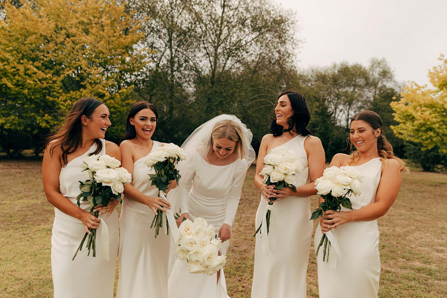 Vinka Design Bridal Wear features Real Wedding Matt and Emilia - bride laughs with bridesmaids, bride wearing Audrey gown from Modern Muse Collection with long veil