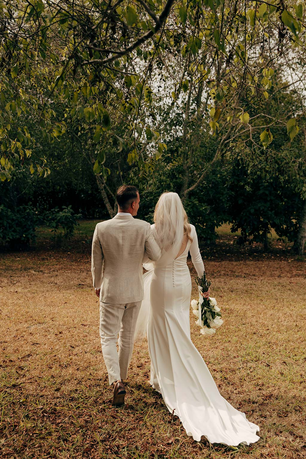 Vinka Design Bridal Wear features Real Wedding Matt and Emilia - bride and groom walk away, bride wearing bespoke Audrey gown from Modern Muse Collection with beautiful long train flowing behind her