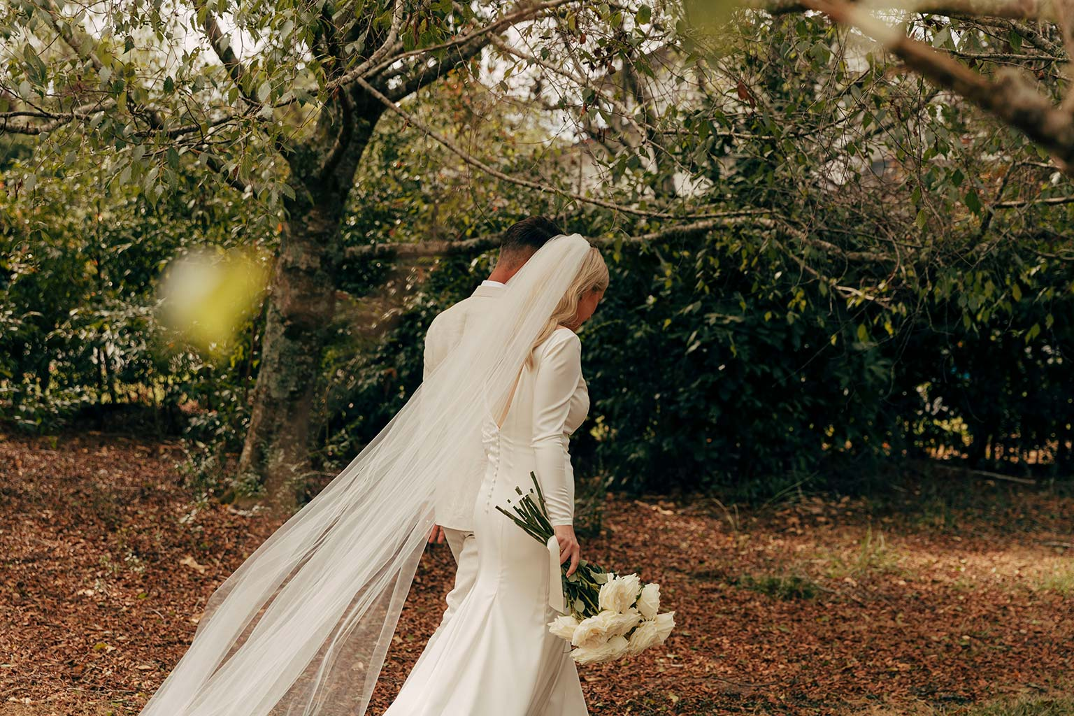 Vinka Design Bridal Wear features Real Wedding Matt and Emilia - bride and groom walk, bride wearing bespoke Audrey gown from Modern Muse Collection with beautiful long veil flowing behind her