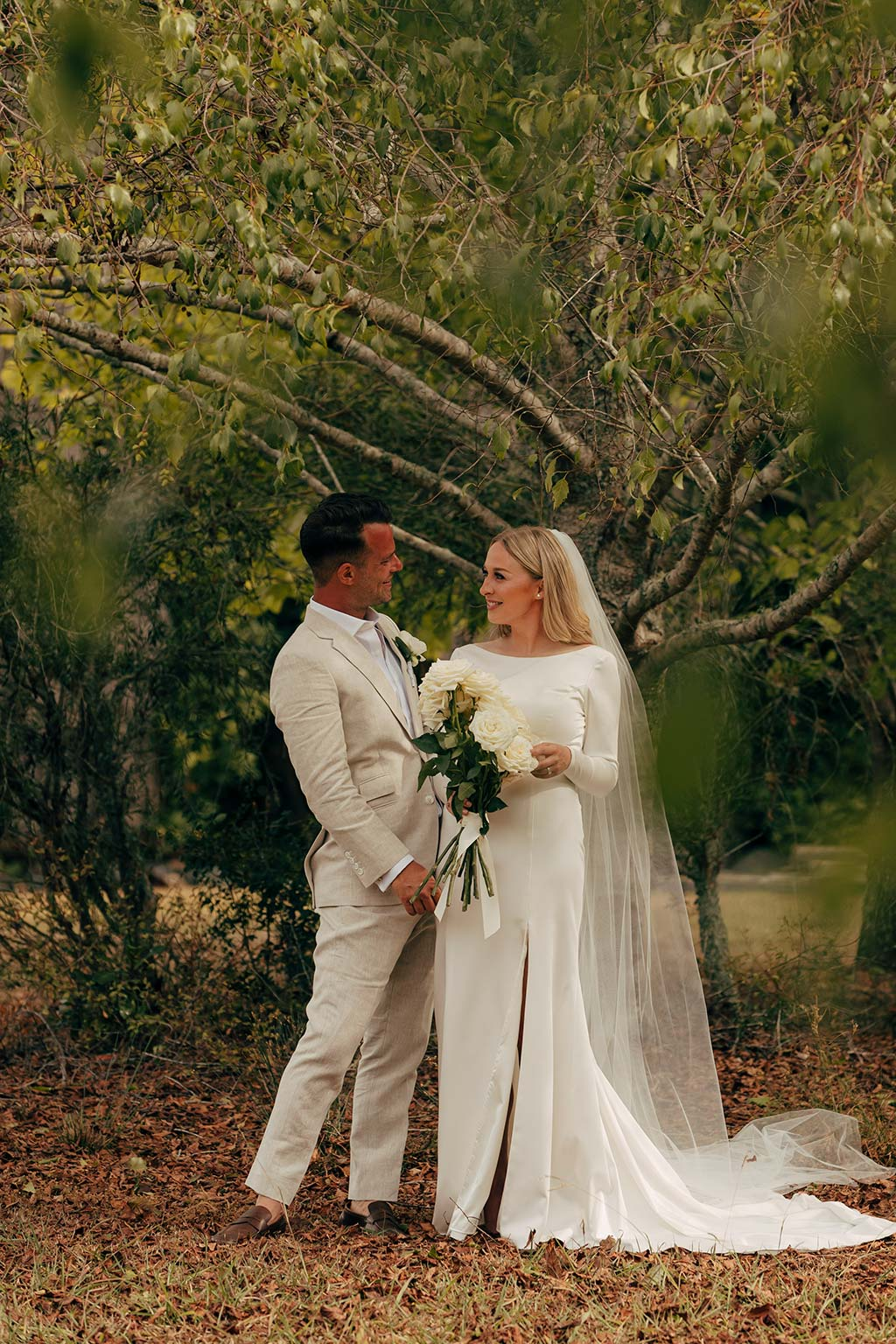 Vinka Design Bridal Wear features Real Wedding Matt and Emilia - bride and groom embrace, bride wearing bespoke Audrey gown from Modern Muse Collection with beautiful long train flowing to her side