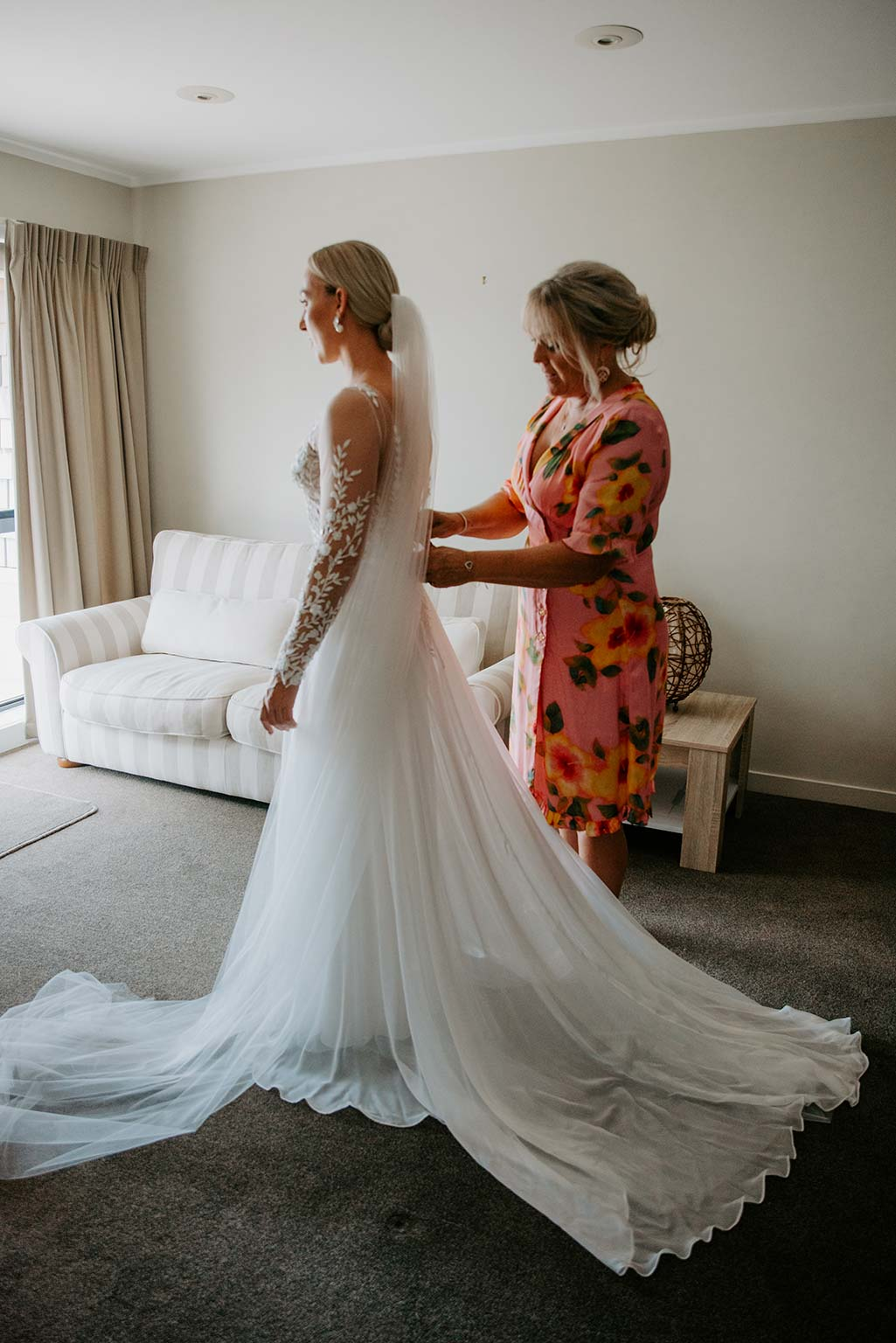 Vinka Design Features Real Weddings - bride getting ready - wearing a bespoke Makaira gown with silk-chiffon and tulle overskirt giving her a beautiful train which could be removed later on to reveal a floor length party dress