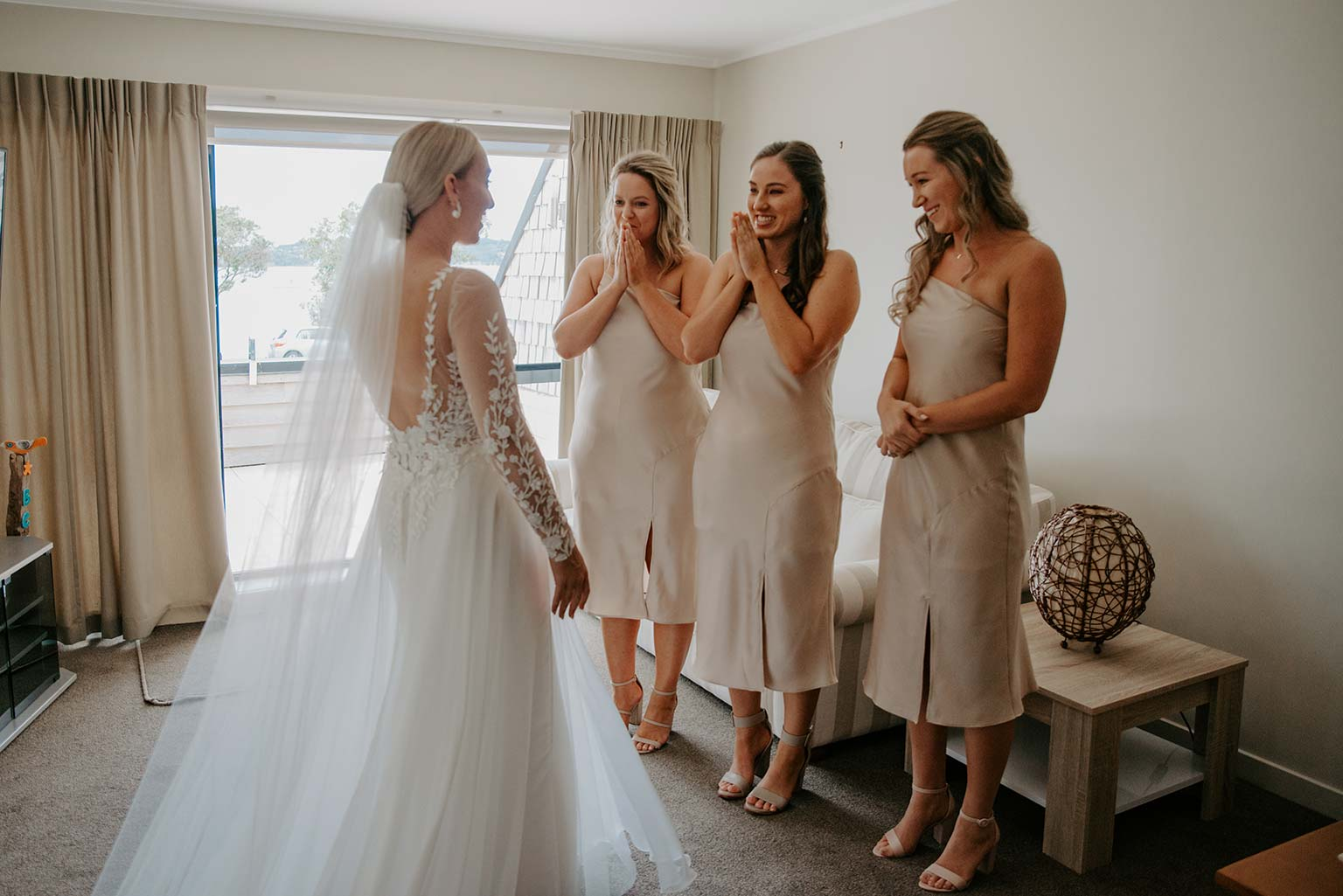 Vinka Design Features Real Weddings - bridesmaids see bride for the first time - wearing a bespoke Makaira gown with silk-chiffon and tulle overskirt giving her a beautiful train which could be removed later on to reveal a floor length party dress