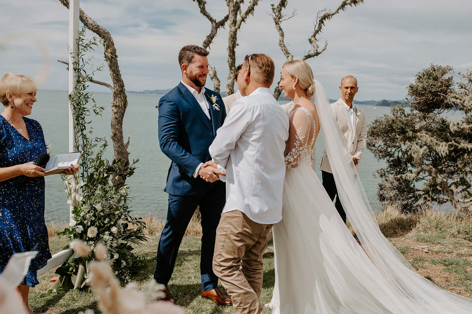 Vinka Design Features Real Weddings - bride and groom at outdoor ceremony next to the ocean - wearing a bespoke Makaira gown with silk-chiffon and tulle overskirt giving her a beautiful train which could be removed later on to reveal a floor length party dress