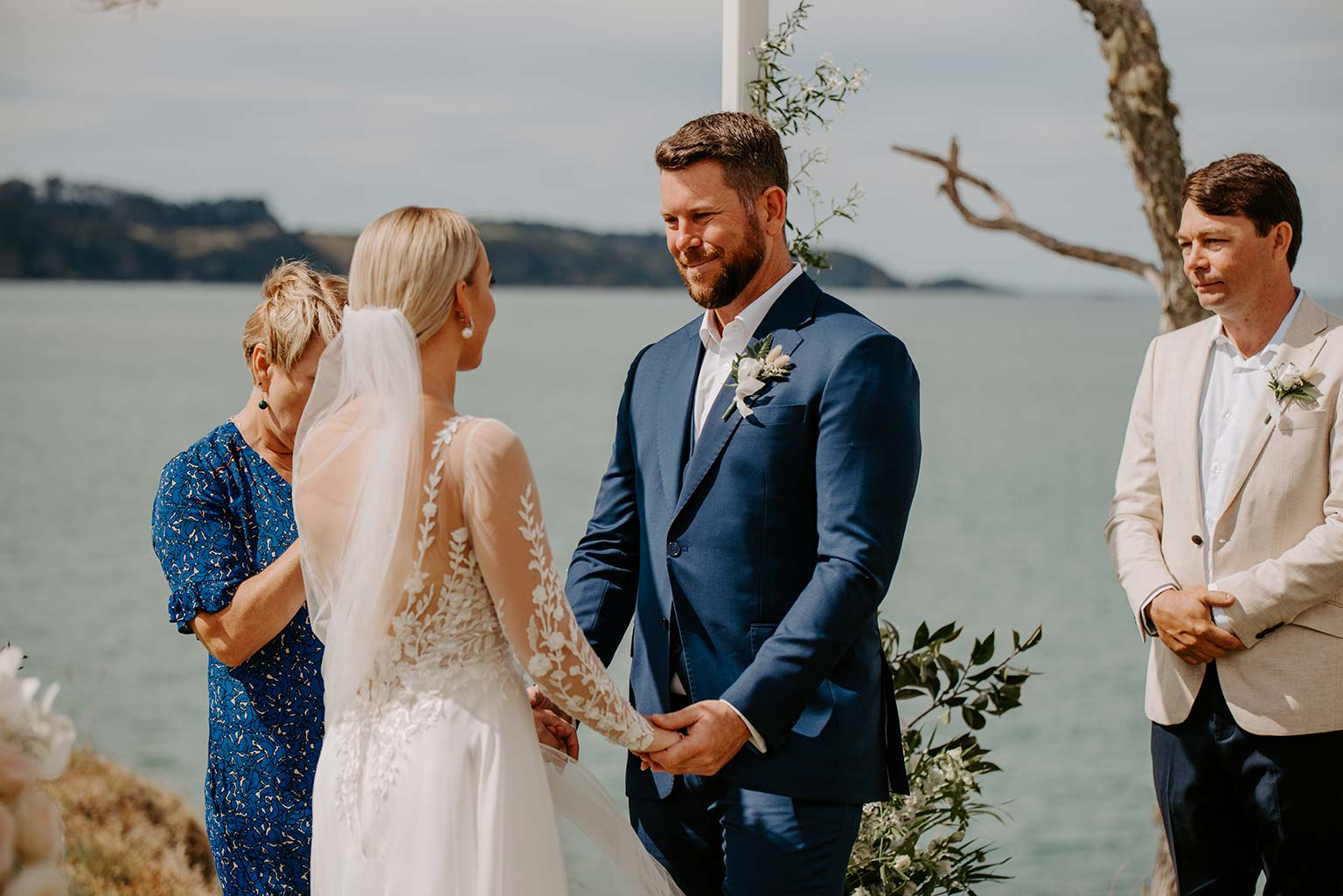 Vinka Design Features Real Weddings - bride and groom take their vows - bride wearing a bespoke Makaira gown with silk-chiffon and tulle overskirt giving her a beautiful train which could be removed later on to reveal a floor length party dress