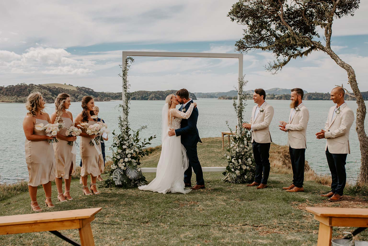Vinka Design Features Real Weddings - bride and groom kiss at ceremony - bride wearing a bespoke Makaira gown with silk-chiffon and tulle overskirt giving her a beautiful train which could be removed later on to reveal a floor length party dress
