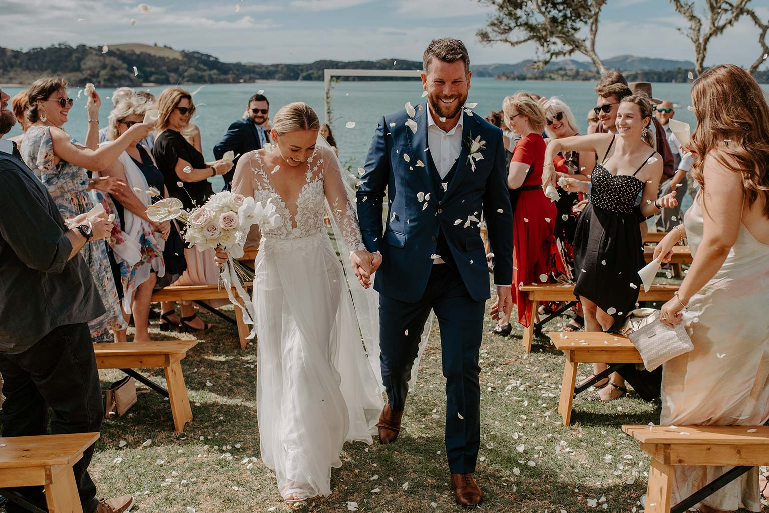 Vinka Design Features Real Weddings - bride and groom walk down the aisle - bride wearing a bespoke Makaira gown with silk-chiffon and tulle overskirt giving her a beautiful train which could be removed later on to reveal a floor length party dress