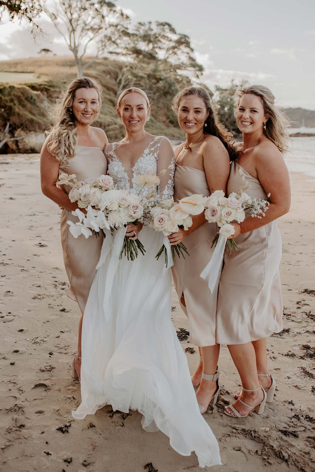 Vinka Design Features Real Weddings - bride poses with bridesmaids - wearing a bespoke Makaira gown with silk-chiffon and tulle overskirt giving her a beautiful train which could be removed later on to reveal a floor length party dress