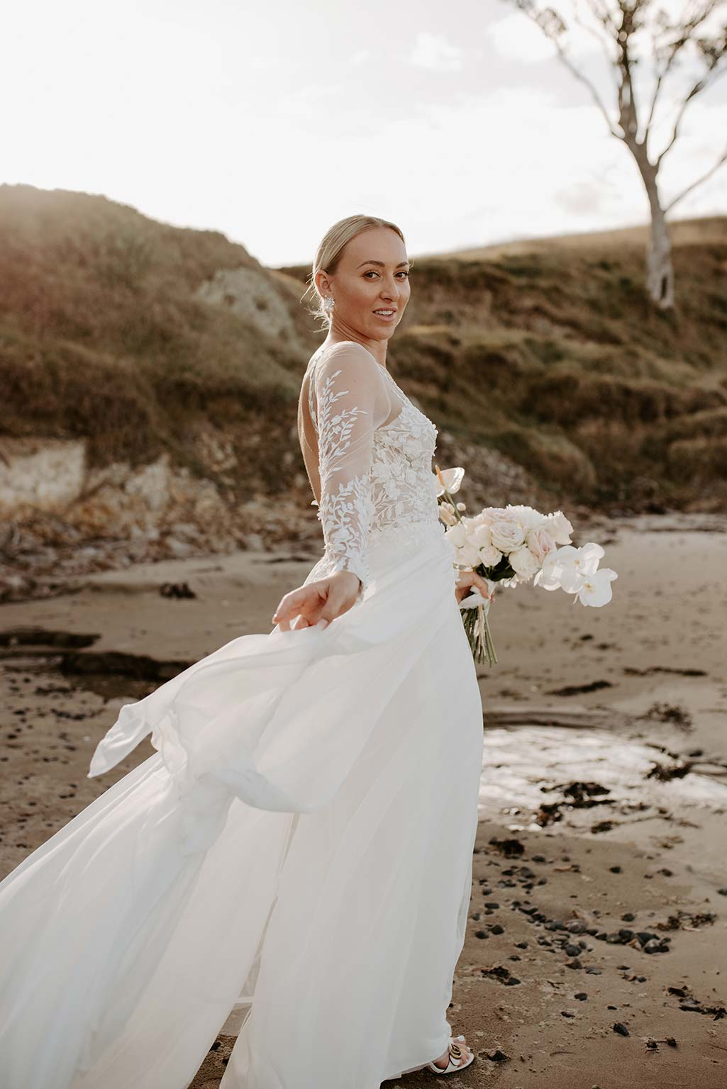 Vinka Design Features Real Weddings - bride poses next to the ocean - wearing a bespoke Makaira gown with silk-chiffon and tulle overskirt giving her a beautiful train which could be removed later on to reveal a floor length party dress